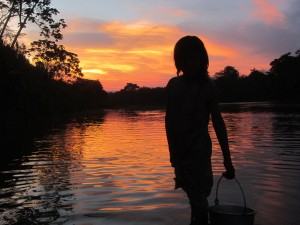 Tsimane' kid fetching water in a river in Bolivian Amazonia.