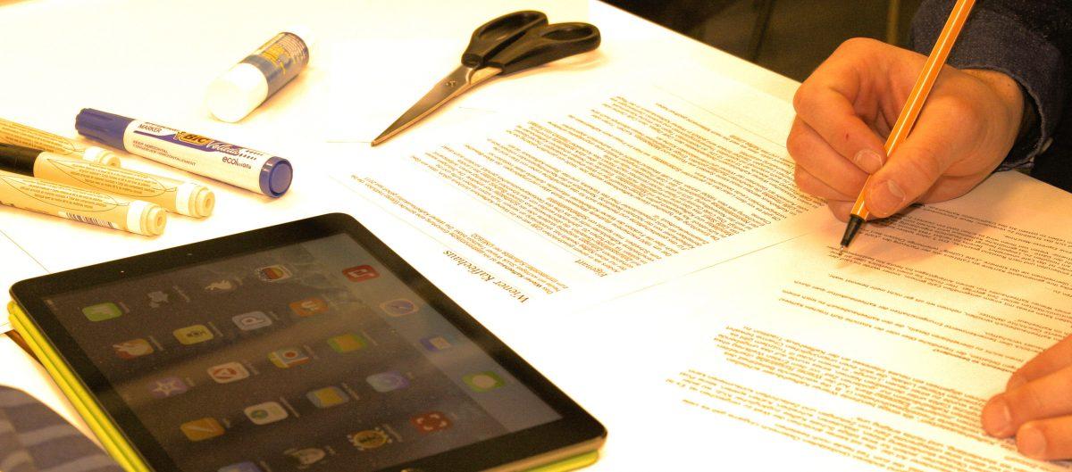 Pöydällä iPad, sakset ja monisteita.