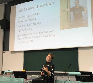 Johanna avaa juhlaseminaarin, taustalla seminaarin ohjelma