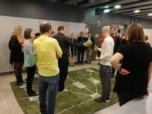 Osallistujat seisovat raideverkkoa esittävällä alustalla ja pohtivat miten pääsevät asemalta toiselle