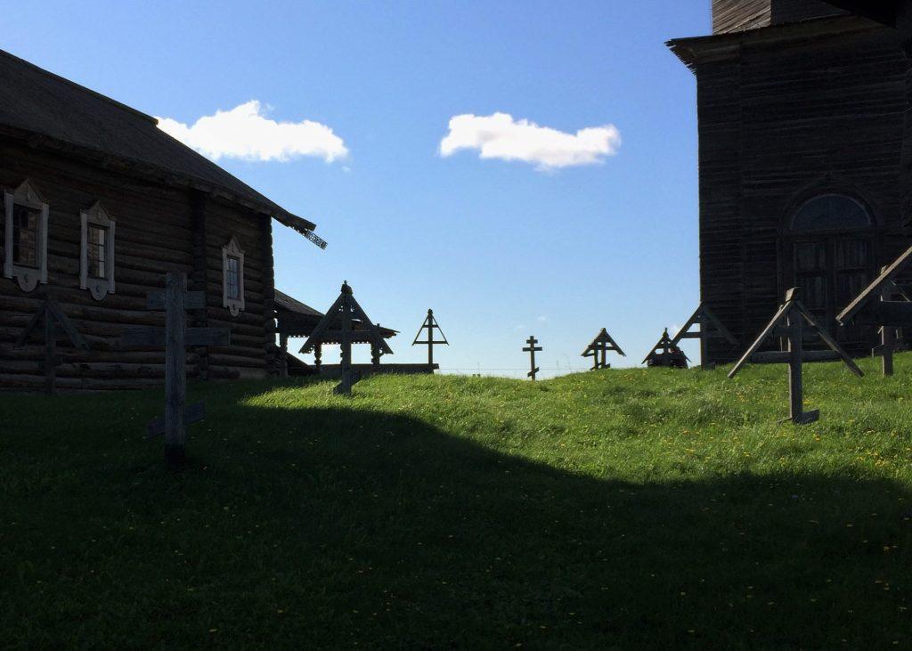 Perinteisiä hatullisia karjalaisia puuristejä aurinkoisella kirkkopihalla
