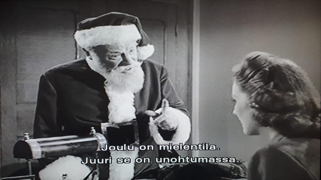 """Kuvassa joulupukki ja nainen, joulupukki sanoo: """"Joulu on mielentila. Juuri se on unohtumassa."""""""