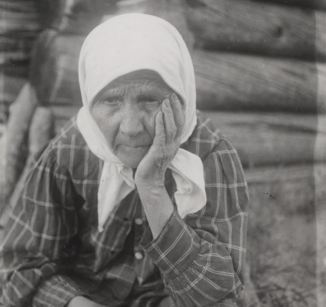 Vanha nainen istuu hirsitalon seinustalla käteensä nojaten. Ilme on surumielinen tai kaihoisa.