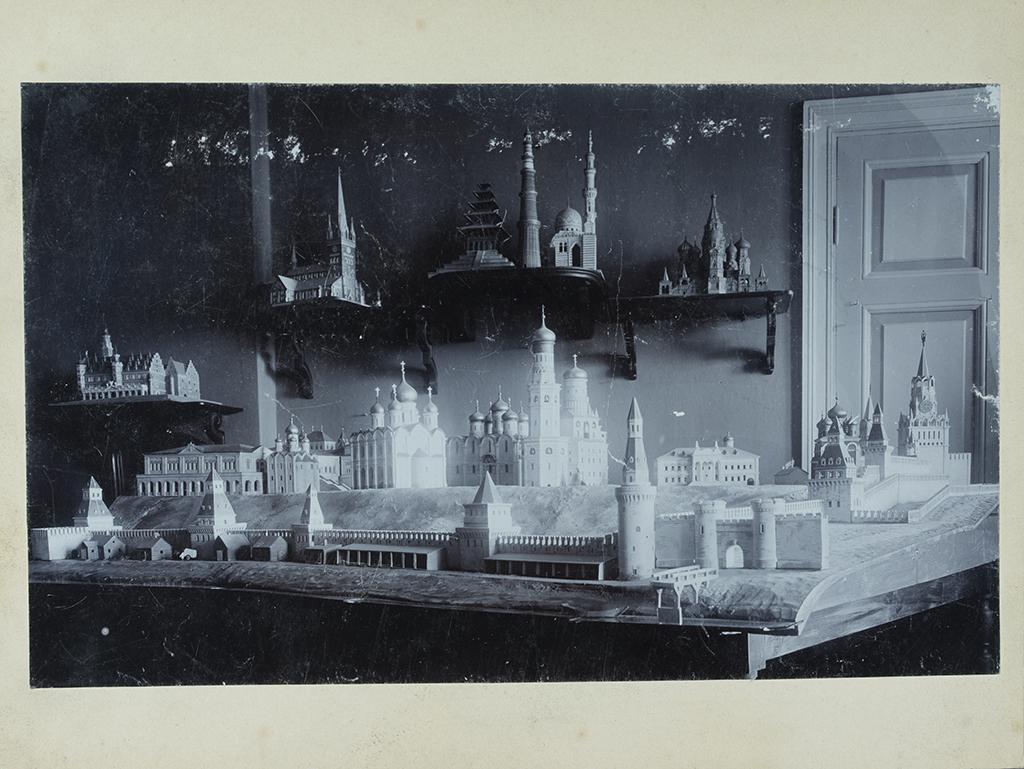 Ett svartvitt foto av en miniatyrmodellutställning med modeller på bordet och på väggfasta ställningar.