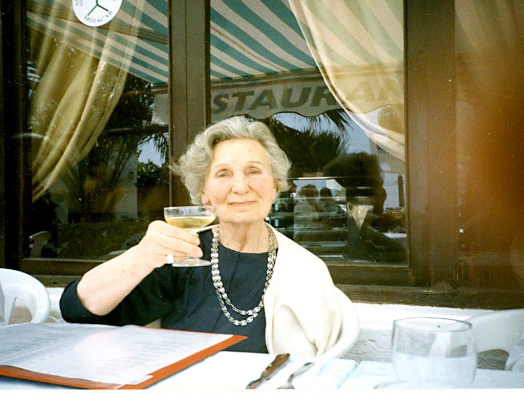 En kvinna med grått hår sitter vid borden vinglas i handen.
