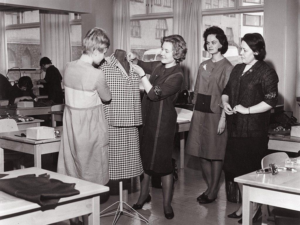 Ett svart-vitt foto av fyra damer som tittar på en färdig klänning på en torso i klassrummet.