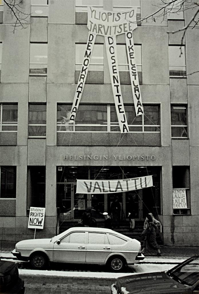 """Administrationsbyggnaden med en bil framför. Studenter på trappan. I fönstren och vid dörren hänger banderoller med budskap som """"Yliopisto tarvitsee demokratiaa, dosentteja, oikeusturvaa"""" (""""Universitetet behöver demokrati, docenter, rättssäkerhet""""), """"Student rights now"""", """"Vallattu"""" (""""Ockuperad""""), """"Tervetuloa töihin!"""" (""""Välkommen till arbetet"""" eller """"Välkommen att arbeta"""") och """"Kenen laulua laulat, Taxell!"""" (""""Vems sång sjunger du, Taxell!"""")."""