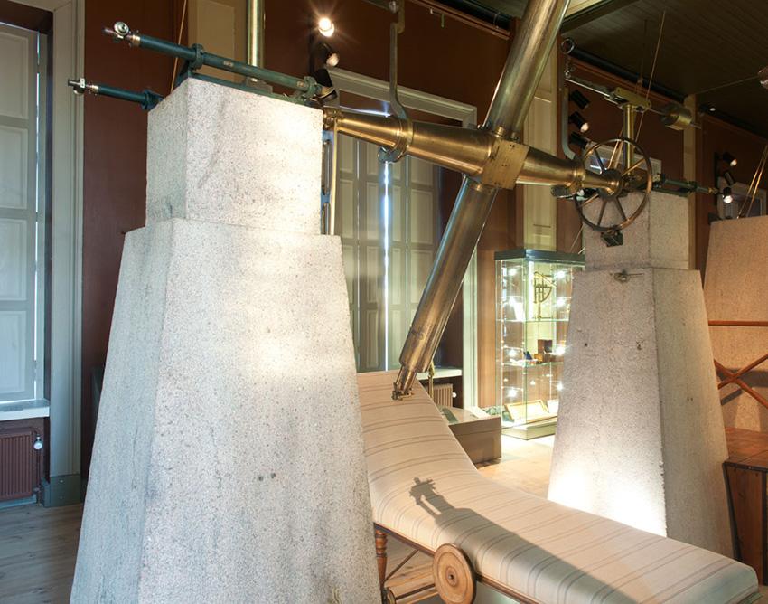 Ett gammalt teleskop som är fäst vid två stora stenpelare. Under teleskopet finns en sängliknande möbel som är högre i ena änden så att man halvligger i den.