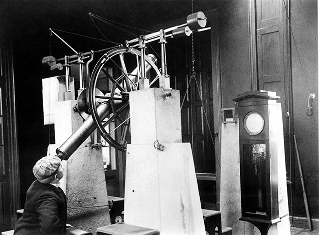 En man i keps tittar i ett teleskop som sitter på två stora stenpelare. Till höger syns en klocka som är fäst vid en stenpelare.