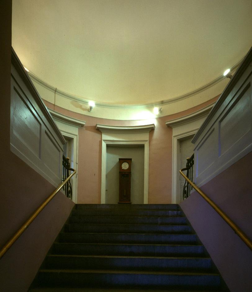 I entréhallen går en trappa upp till en trappavsats, där det hänger ett stort väggur.