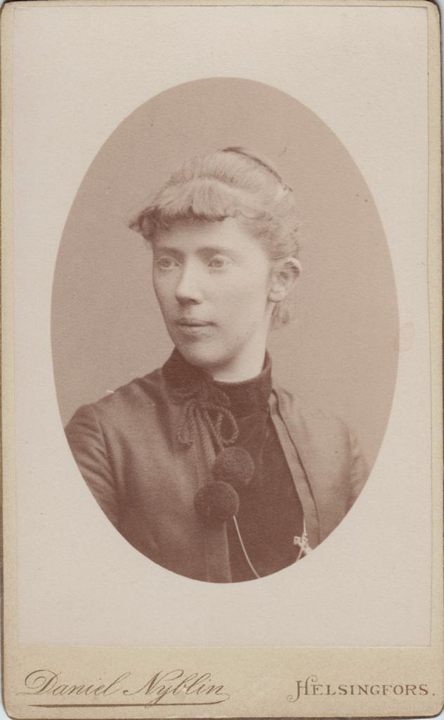 Närbild av en ung kvinna som tittar en aning åt sidan. Kvinnan har håret uppsatt i en knut och är klädd i en klänning med hög krage och två stora bollformiga tofsar som hänger ner.
