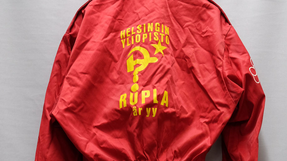 Symboler som hänvisar till Sovjetunionen, en hammare och en spira som stiliserats som ett frågetecken samt text tryckta på ett rött, lite skrynkligt klädesplagg.