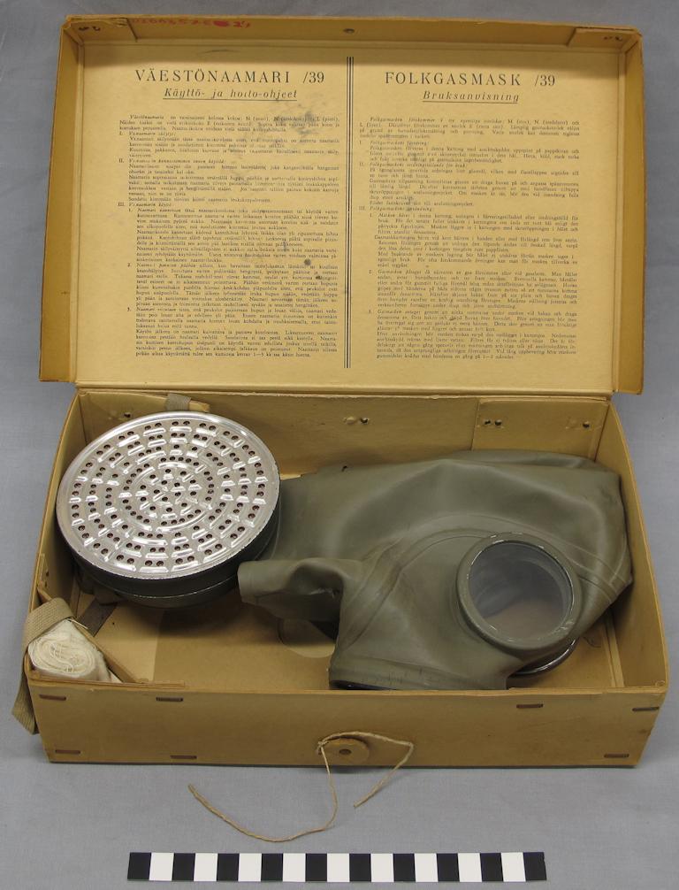En grön gasmask i en pappkartong. Innanför locket har man tryckt bruksanvisningar för masken på finska och svenska.