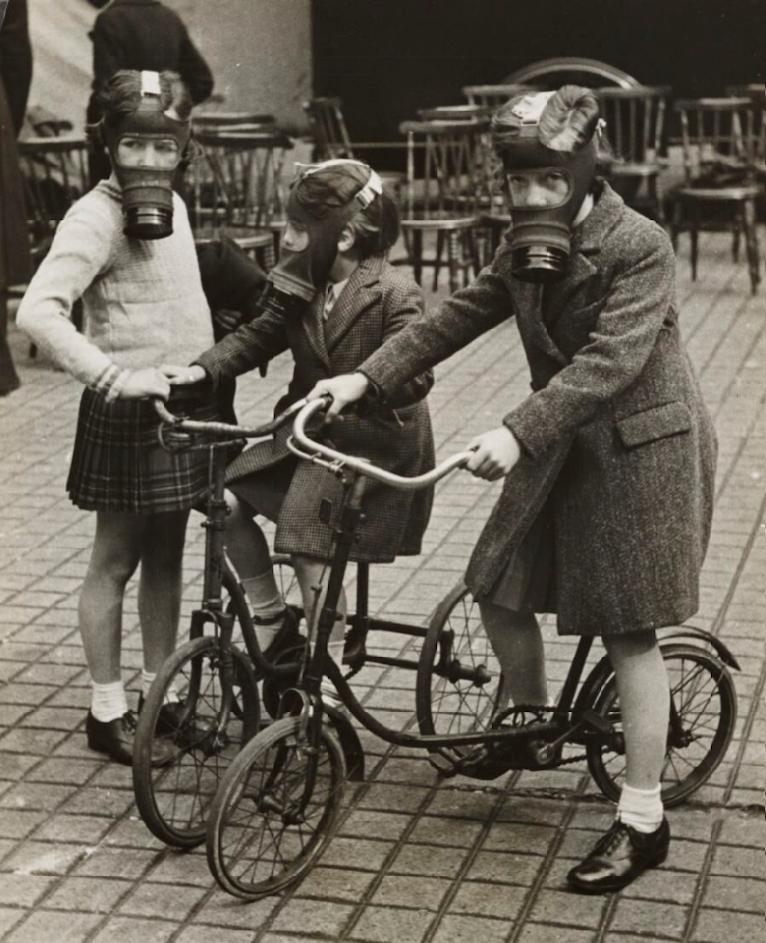 Tre små flickor på gatan med gasmasker på sig. Två av flickorna har en cykel. I bakgrunden syns många trästolar. Fotot är svartvitt.