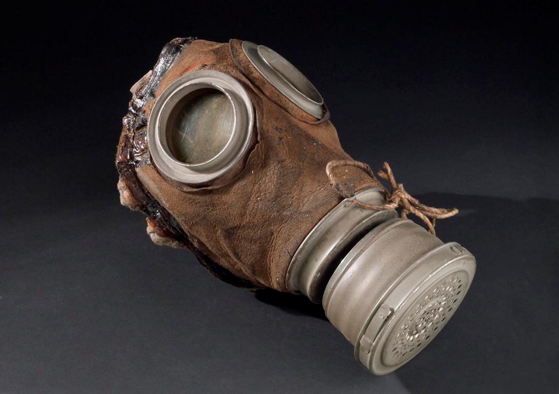 En tidig gasmask där maskdelen är av brunt skinn. Gasmasken har runda ögonöppningar med metallram och ett metallfilter.