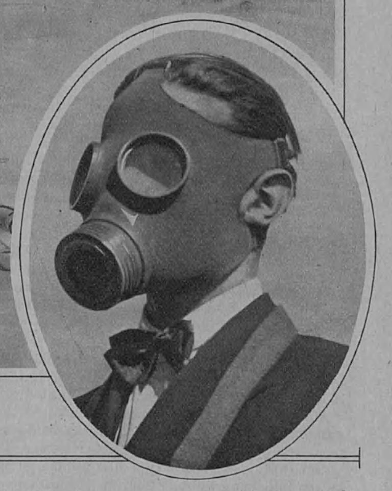 Ett ovalt tidningsfoto av en mansbyst med en finsk civil gasmask på ansiktet. Mannen är klädd i en vit skjorta och en mörk kavaj. Han har en fluga runt halsen. Det löper en rem över mannens axel, troligen bärremmen till gasmaskfodralet. Fotot är svartvitt.