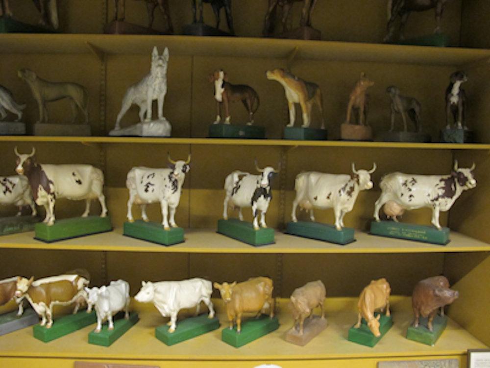 Små skulpturer av kor och hundar som står på gula hyllor.