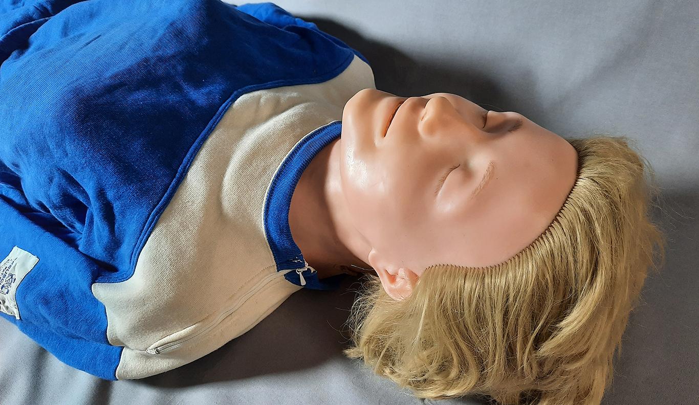 Överkroppen av övningsdockan Anne i träningsdräkt fotograferad från huvudets riktning.