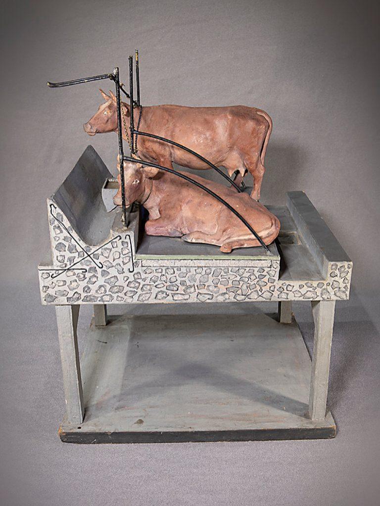 Bilden visar en miniatyrmodell med två bruna kor i en båsladugård, sett från sidan. Korna står med bringan åt vänster. Den bakre kon står och den främre av dem ligger. Under korna finns gödselstaden, ett stort tomt utrymme. På modellen har man ritat var stödkonstruktionerna ska vara. Bakgrunden är grå.