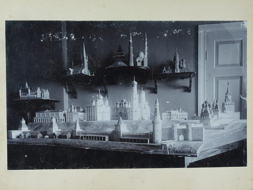 A black-and-white photograph of a scale model exhibition with models on the table and on wall-mounted stands.