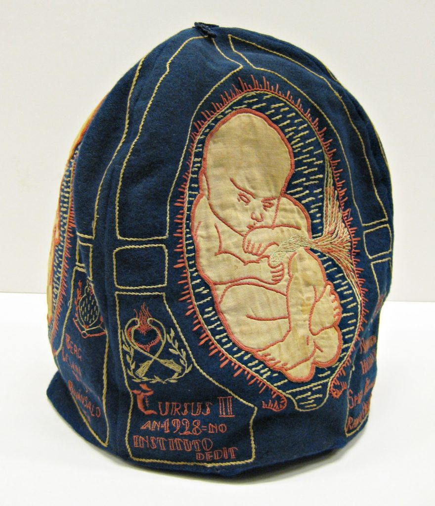 A blue tea cosy with an embroidered fetus on the side.