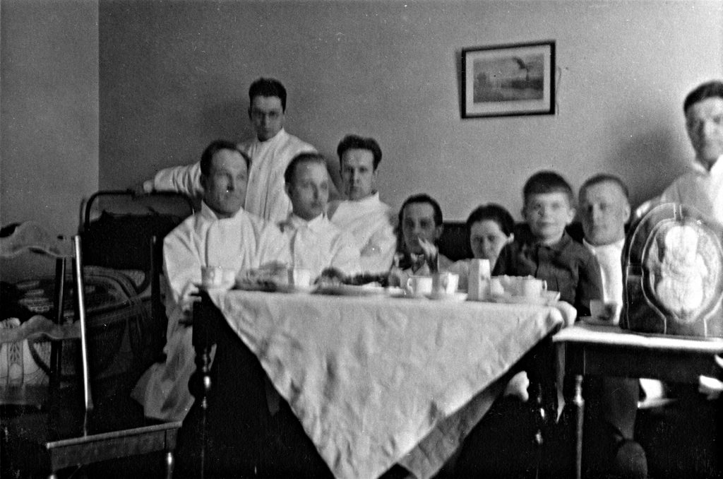 A group photo of physicians around a coffee table. The tea cosy in question is on the table.