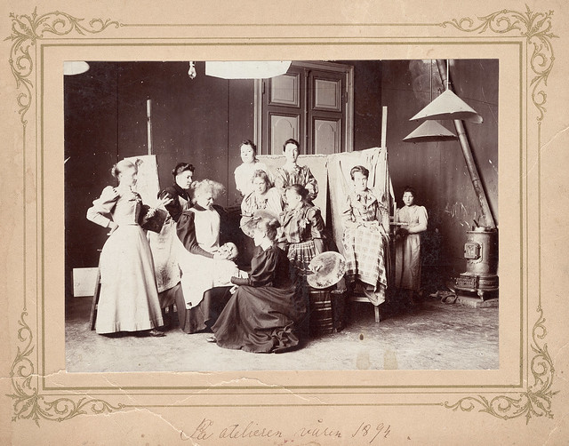 A black and white photograph of 10 women, standing and sitting. dressed with long skirts. In the background two cloths, a long door and a stove.