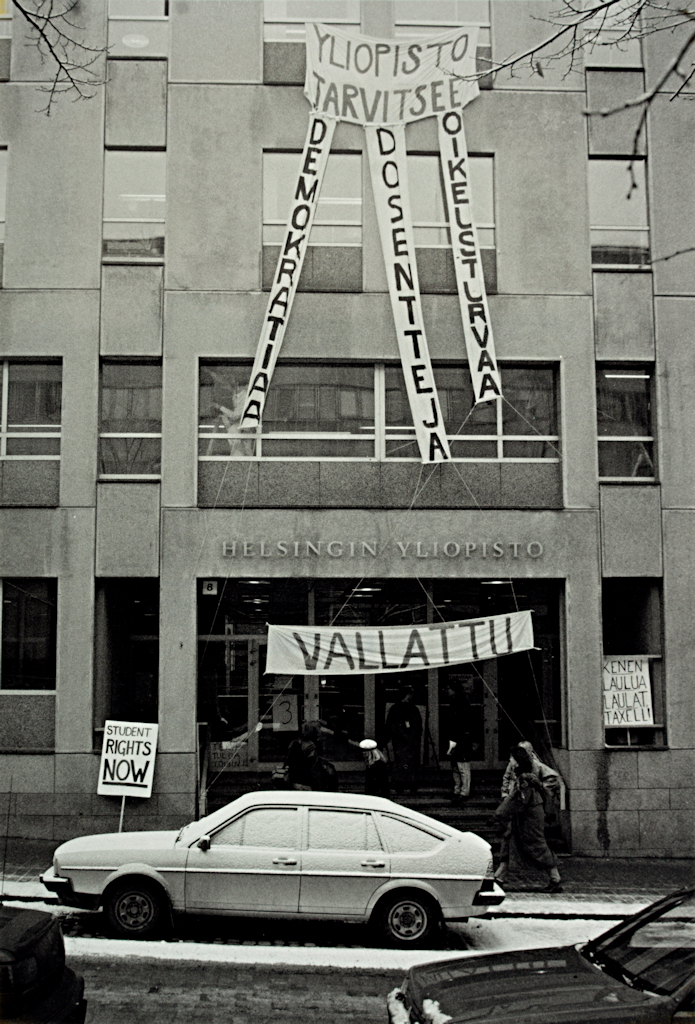 The administration building with a car parked outside and students on the stairs. Banners hanging from the windows and at the entrance proclaim: Yliopisto tarvitsee demokratiaa, dosentteja, oikeusturvaa ('The University needs democracy, docents, legal protection'), Student rights now, Vallattu ('Occupied'), Tervetuloa töihin ('Welcome to work') and Kenen laulua laulat, Taxell! ('Who's calling your tune, Taxell!').