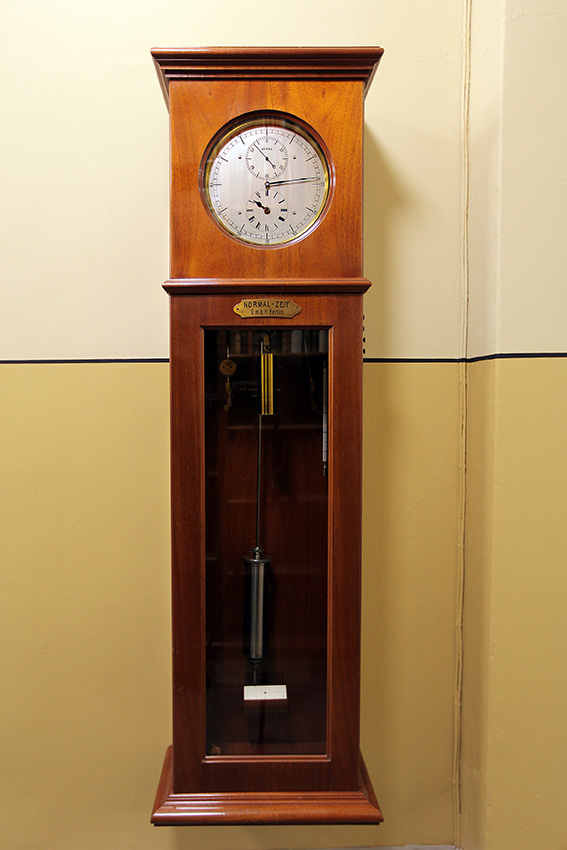 An elongated wall-mounted grandfather clock, with a round, glass-covered clock face in a wooden case and the clock pendulums behind a glass door underneath.