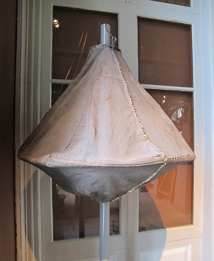 A grey fabric bag with a hoop-like support structure inside and a metal suspension hook at the top.