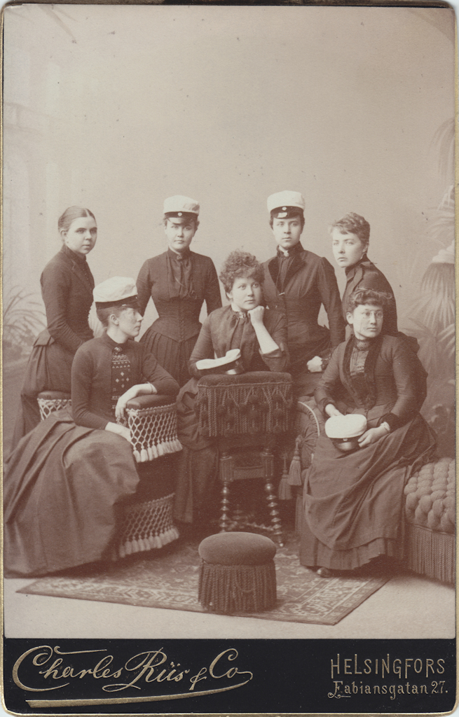 Seven young women, of whom four are standing at the back and the two in the middle are wearing a student cap. Of the three women sitting at the front, the one on the left has turned sideways and is wearing a student cap, while the other two are holding the cap in their laps.
