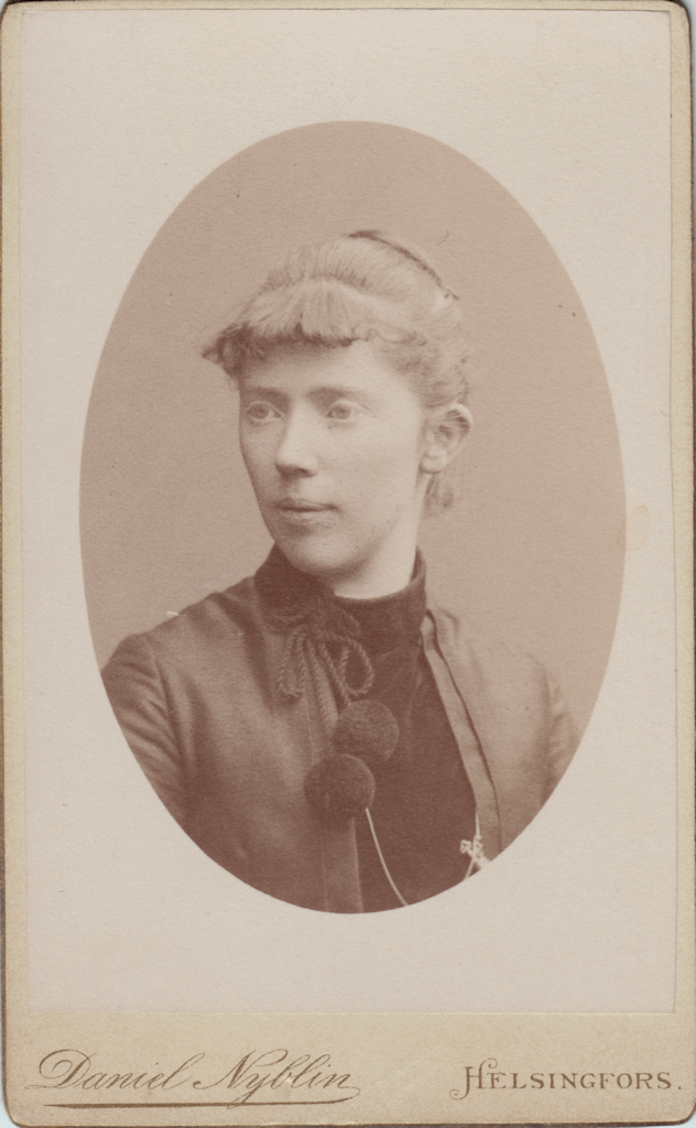 A close-up of a young woman looking slightly to one side. Her hair is in a bun and she is wearing a high-collar dress from which two large tassels are hanging.
