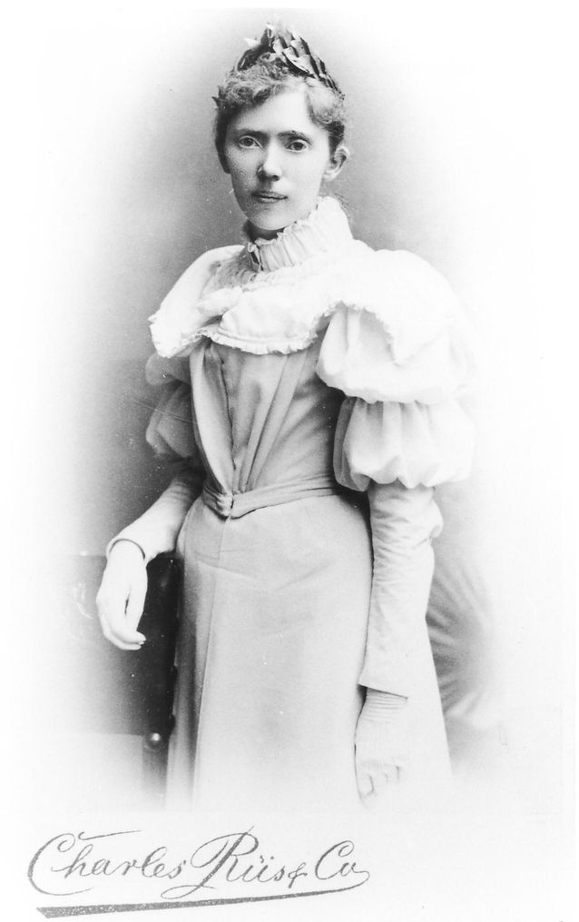 A young woman standing, resting her right elbow lightly on a piece of furniture. Her hair is in a bun, she has a laurel garland on her head and she is wearing a light-coloured, high-necked dress.