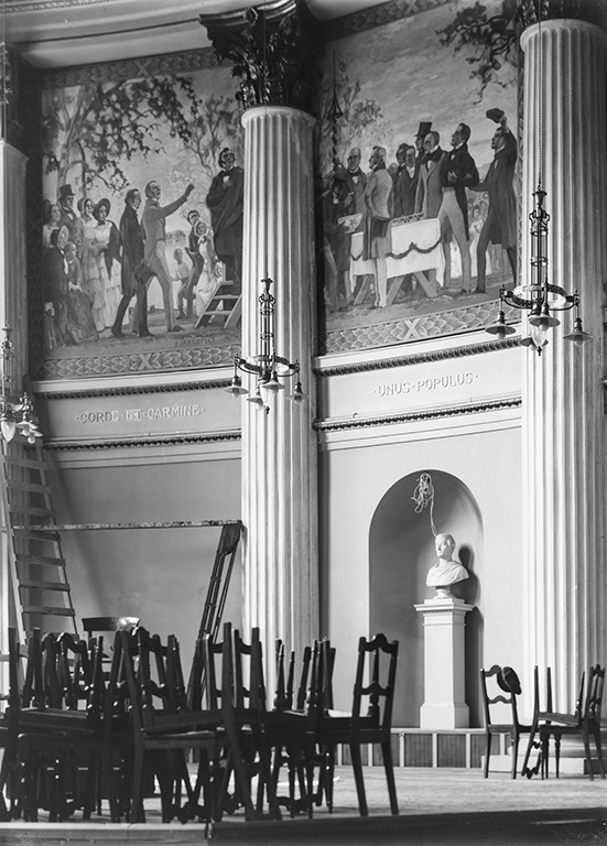 An old photograph of the original Flora Day paintings in the University's Great Hall. The paintings are high on the wall, in the front, stacked chairs.