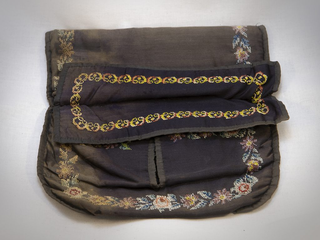 A floral motif circles around the edges of the rectangular purse.