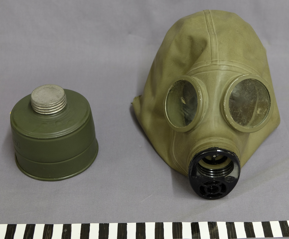On the right is a military-green rubber gas mask, with eyepieces facing towards the photographer. Next to it on the left is a darker green filter cartridge. At the bottom is a scale.