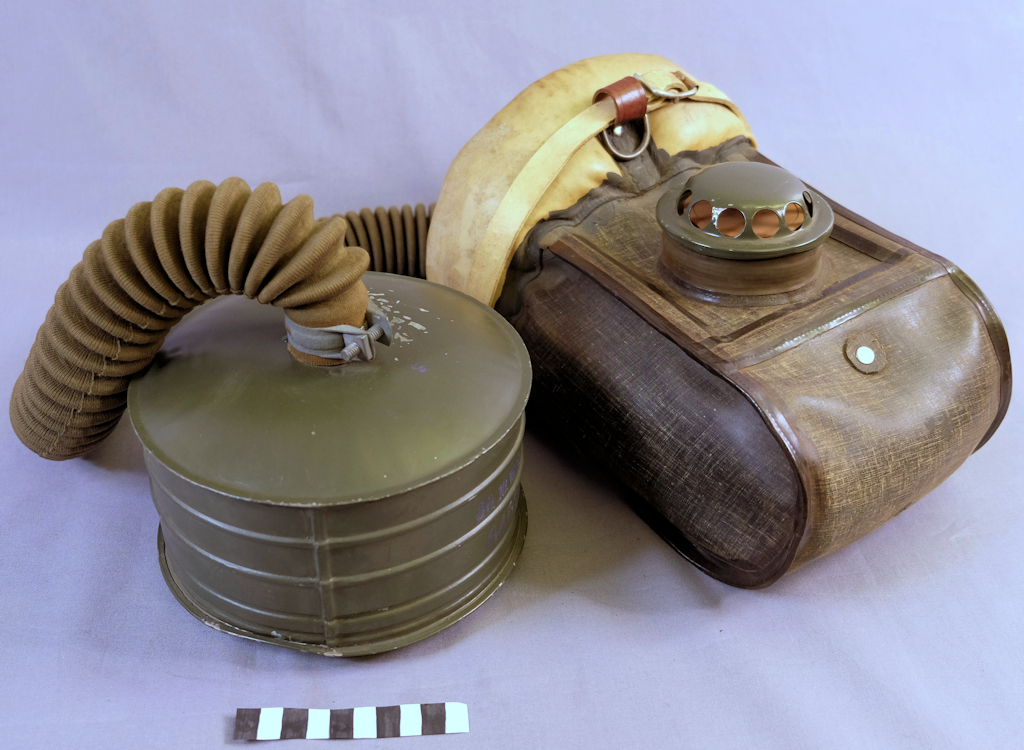 Equine gas mask, including a padded face piece designed to fit over the muzzle as well as a large filter cartridge painted green. The face piece and the filter are connected with a cloth-covered hose.