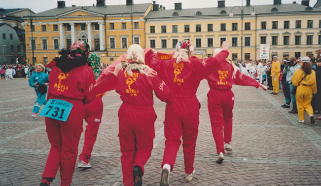 Four young women wearing overalls and headscarves and running side by side on Senate Square from Helsinki Cathedral towards Aleksanterinkatu street. One has the number 731 on her bottom. On the right, members of the audience in yellow, green and white overalls.