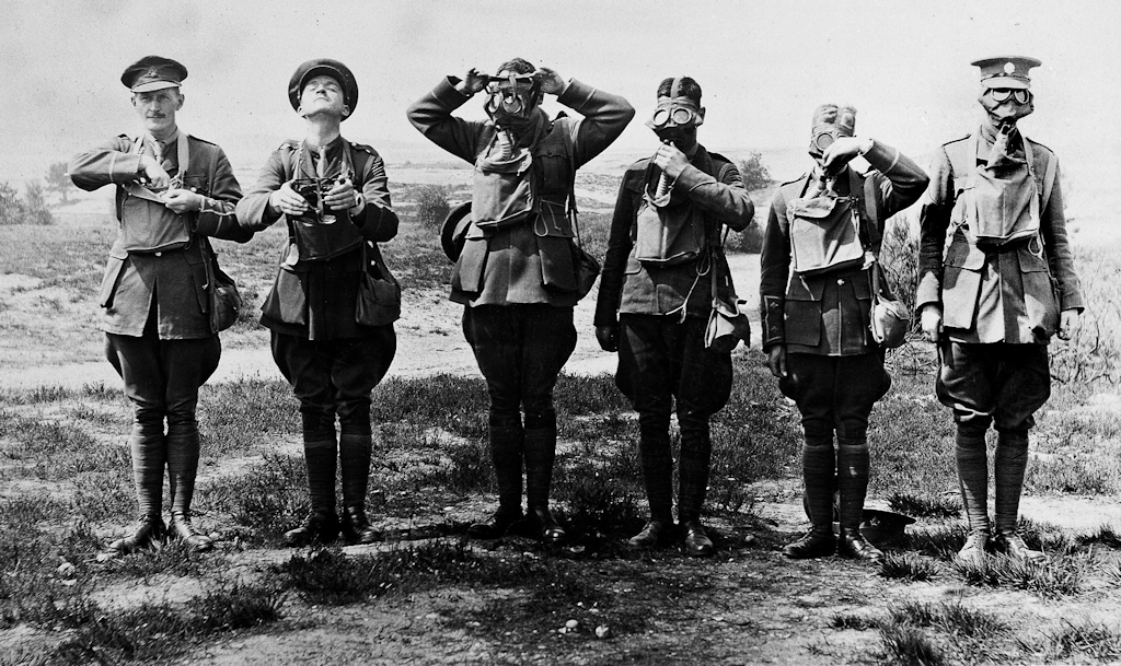 A black-and-white photo of six men in battledress standing side by side outdoors. The men are demonstrating each stage of putting on a gas mask: the first man is taking a mask from a bag around his neck, the second is holding a mask in his hands, the third is placing a mask on his face, the fourth is putting the hose in place, the fifth is making the final adjustments and the sixth is ready.