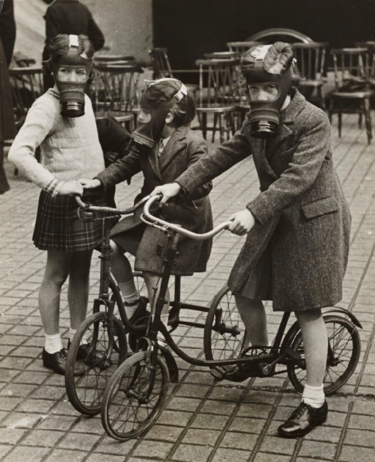 Three little girls on a street wearing gas masks. Two of the girls have a bicycle. Many wooden chairs can be seen in the background. The image is in black and white.
