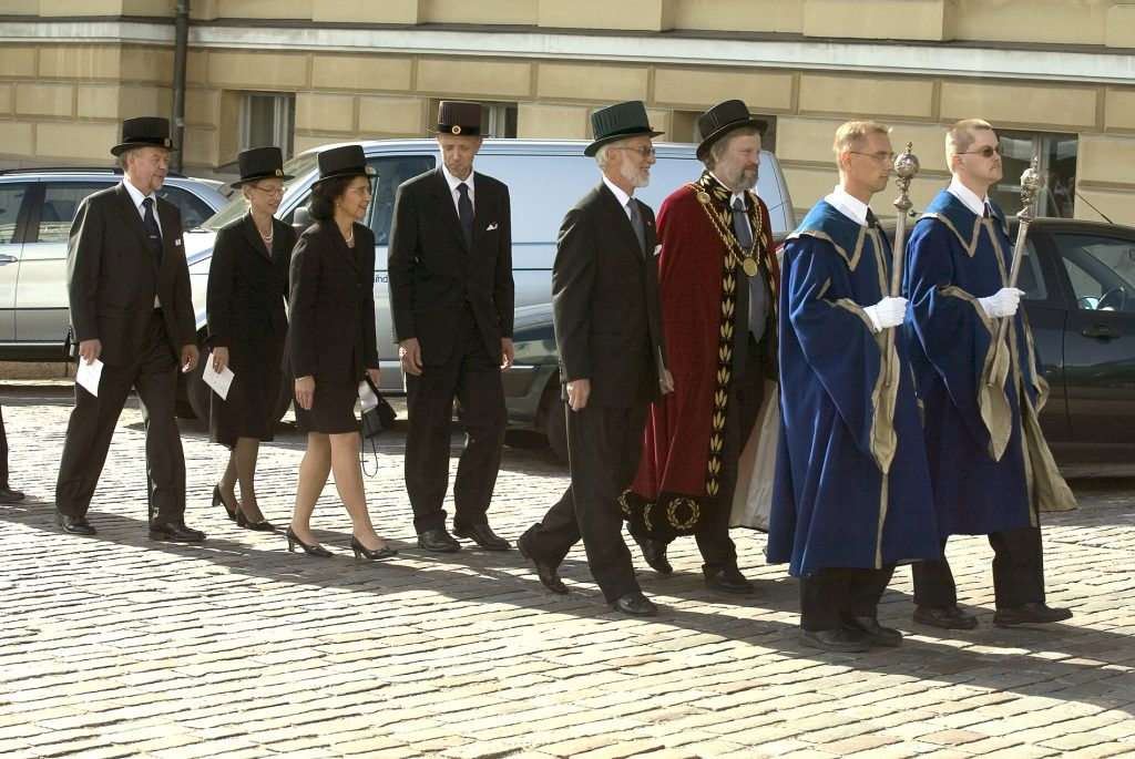 A procession of men and women in festive attire and wearing doctoral hats. Beadles carry sceptres at the head of the procession.