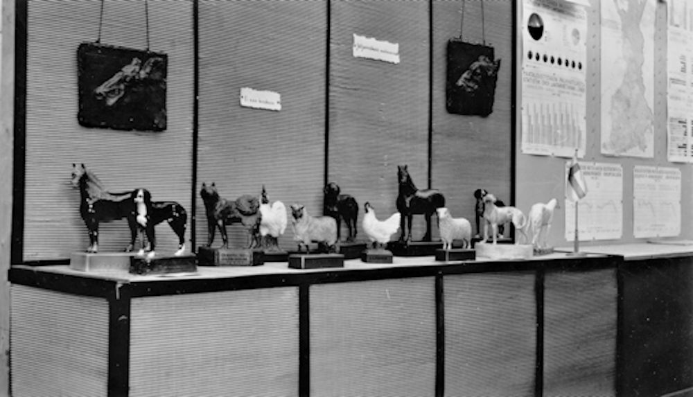 A black-and-white photograph from an exhibition, where various kinds of small sculptures of domestic animals are on display on a table. On the wall behind the table, there are reliefs depicting a cow and a bull, as well as images.