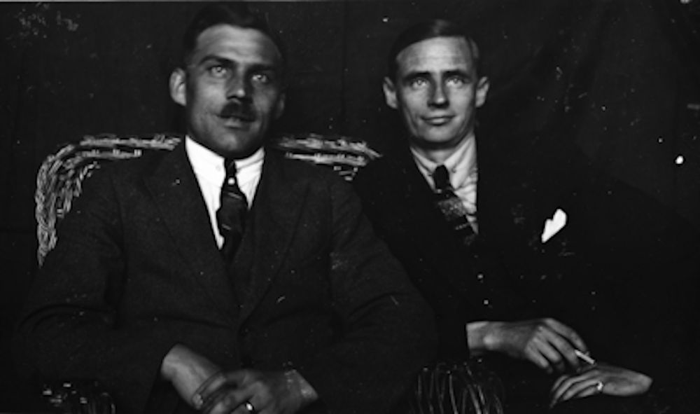 A black-and-white half-length portrait of two men dressed in dark suits and tie, sitting on a rattan sofa, smiling faintly. One is holding an unlit cigarette in his hand.