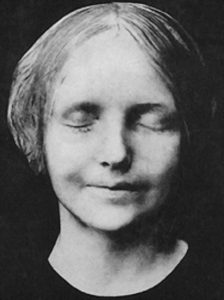 A black-and-white photo of the death mask of a young woman with short hair. Her eyes are closed, and she has a faint smile on her lips.