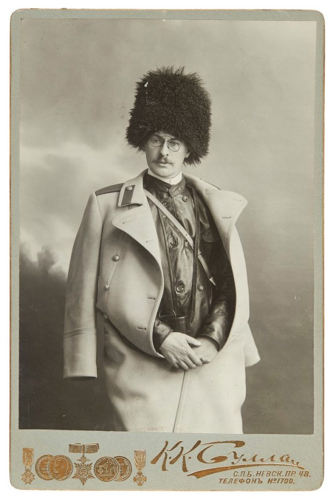 A black-and-white photograph of a young Backmansson, wearing a high fur hat and a light-coloured overcoat draped over his shoulders.