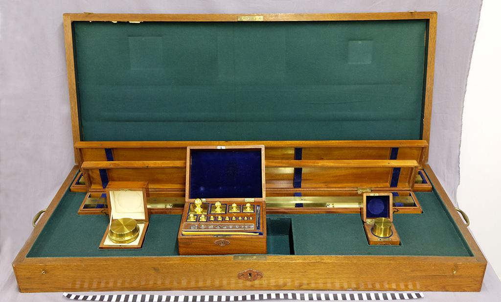An open wooden box, inside measurements made of brass.