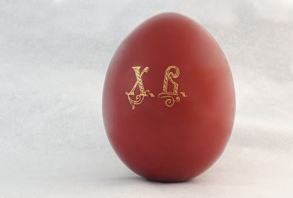 A photograph of a red Easter egg on a white background.