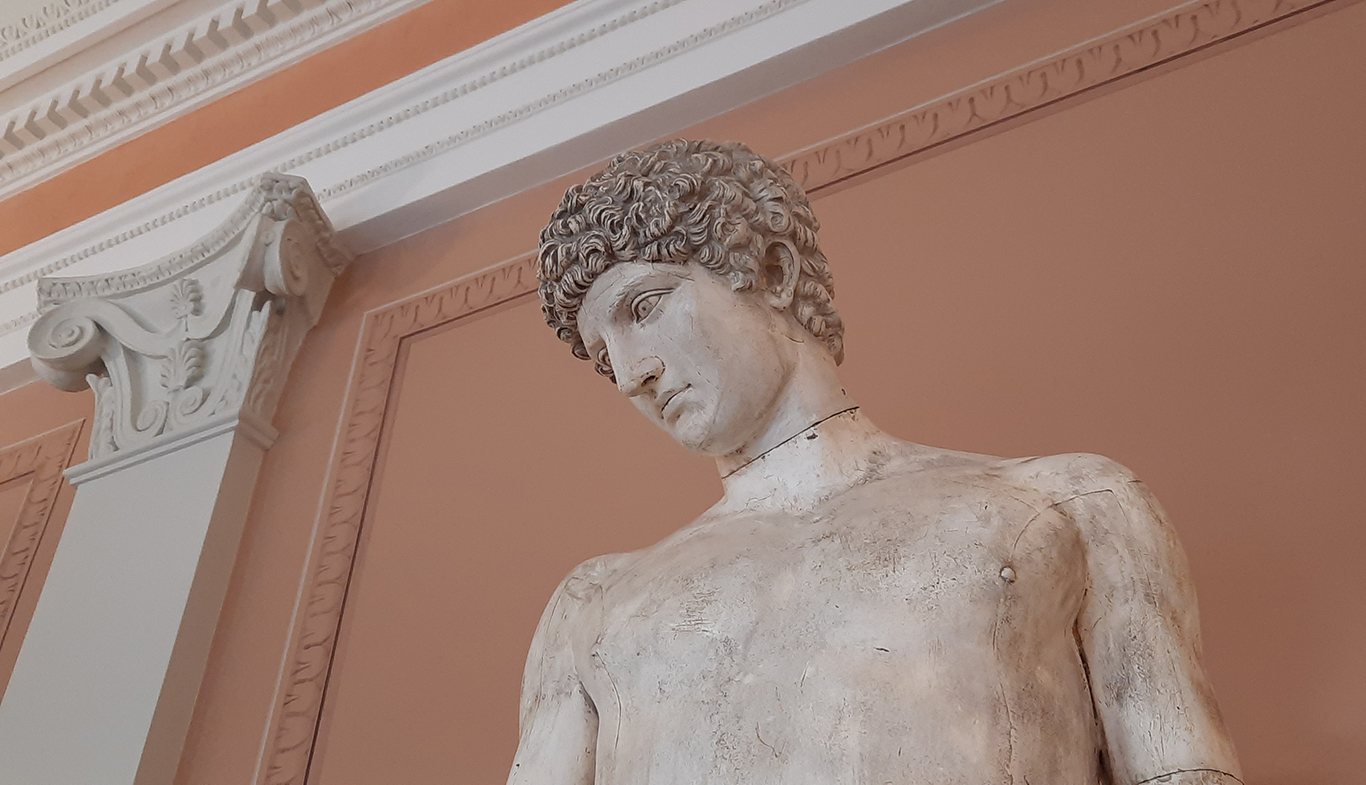 A close-up of the upper body of the statue of Antinous in the University's Main Building. Some wall ornaments and a pilaster can be seen in the background.