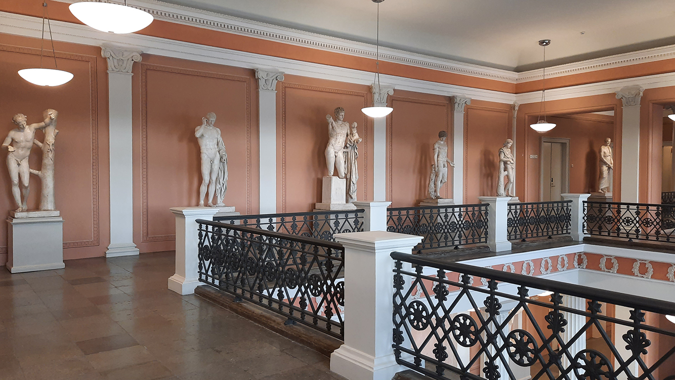 A view from the fourth floor of the University's Main Building. On the right is the vestibule behind a wrought-iron banister, and on the back wall is a row of sculptures in a corridor.