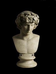 A photo of a marble bust against a black background, showing a young man with a bare upper body, curly hair and a wreath on his head.